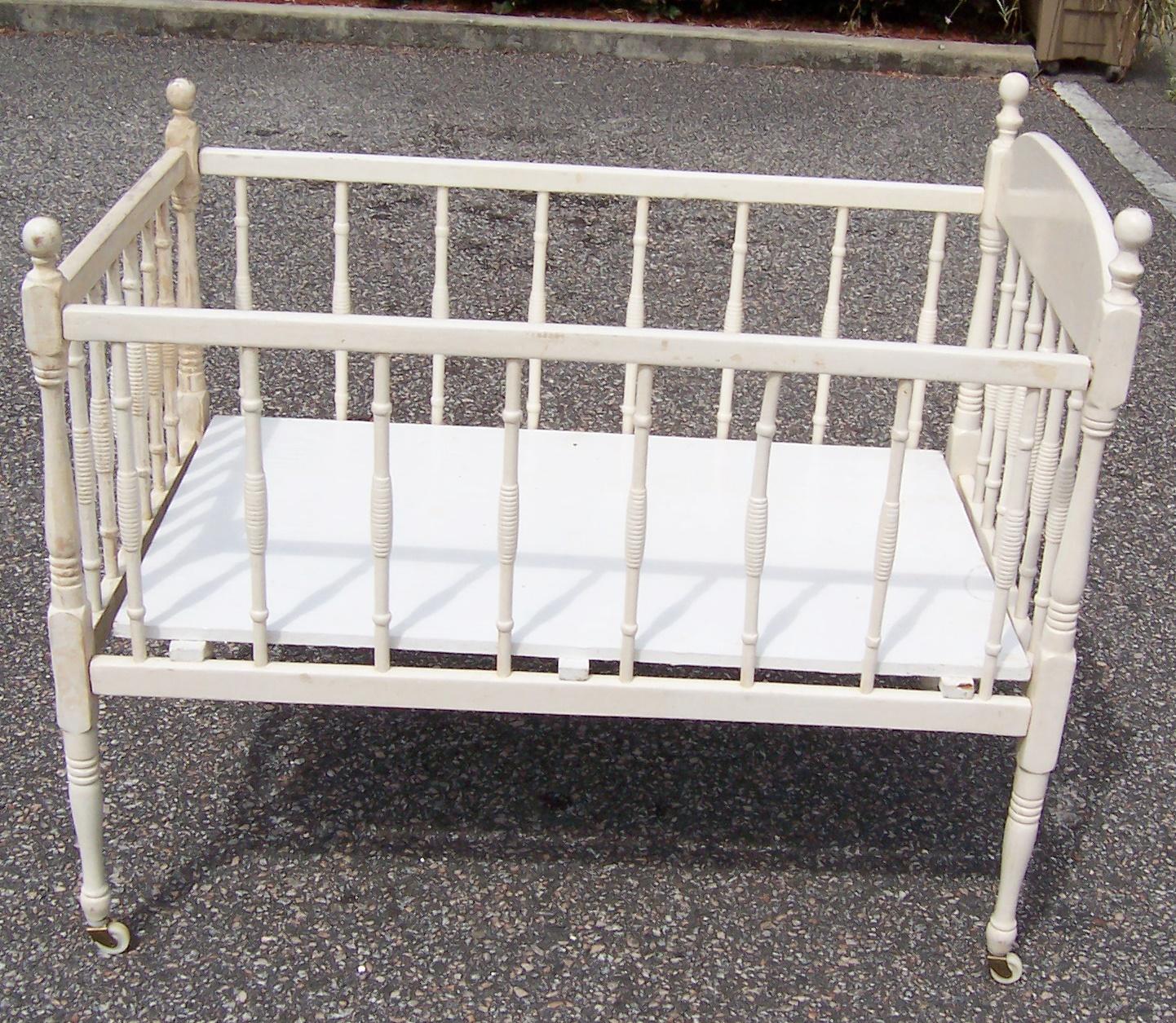 antique white wooden baby crib on wheels -